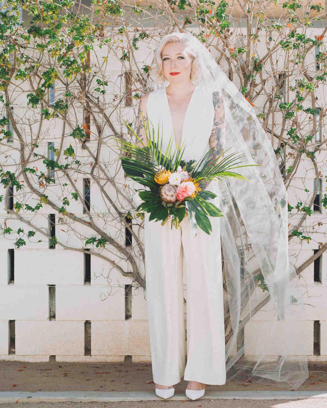 bride in jumpsuit holding bouquet