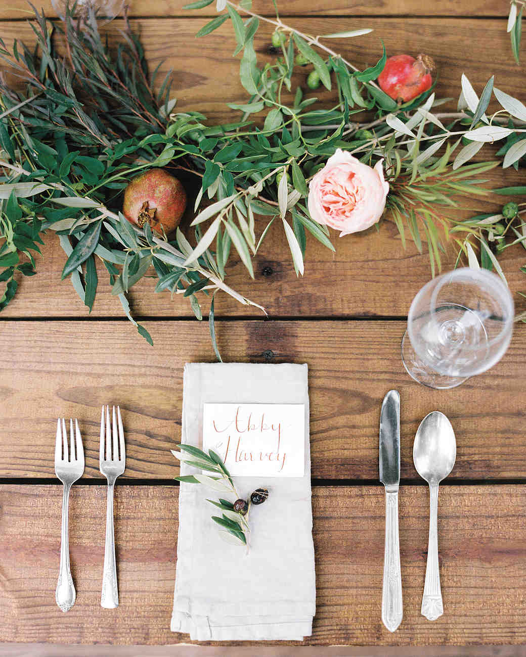 Wood Table with Minimalist Table Setting and Green Foliage