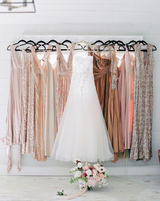 bride's hanging custom mira zwillinger wedding dress with blush and peach tone glittery bridesmaids dresses