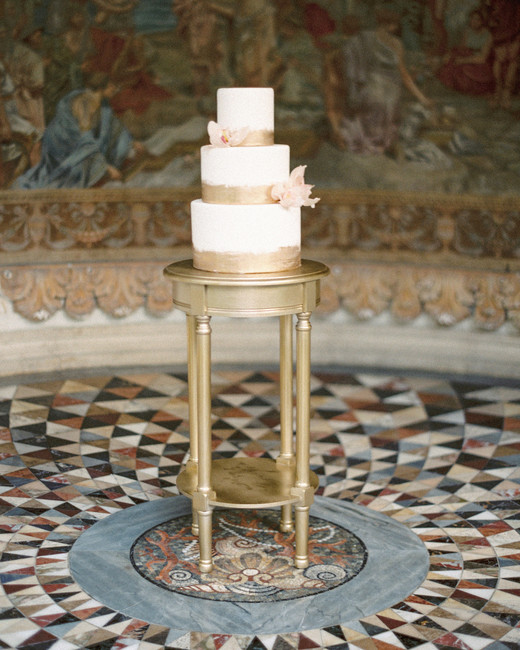 three tiered white wedding cake with gold foil accents and orchid decor
