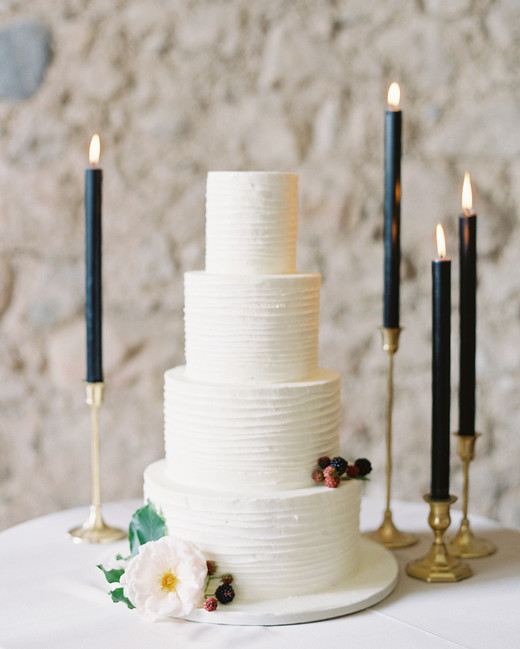 four tier white icing cake with fresh berries decor