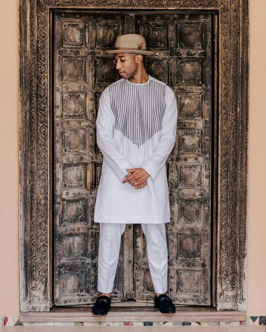 Groom wearing Malian heritage white African Dashiki shirt and pants set