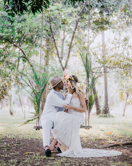 bride and groom siting on wooden swing