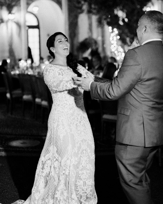 bride and groom smile during first dance at reception