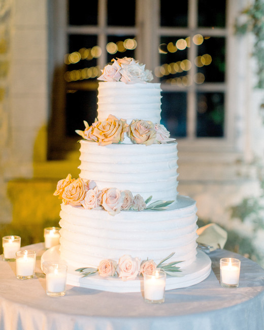 buttercream iced three tiered wedding cake with roses