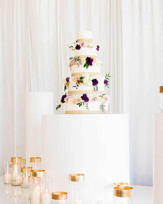 ivory frosted five tiered wedding cake wth gold ribbon accent and fresh floral decor