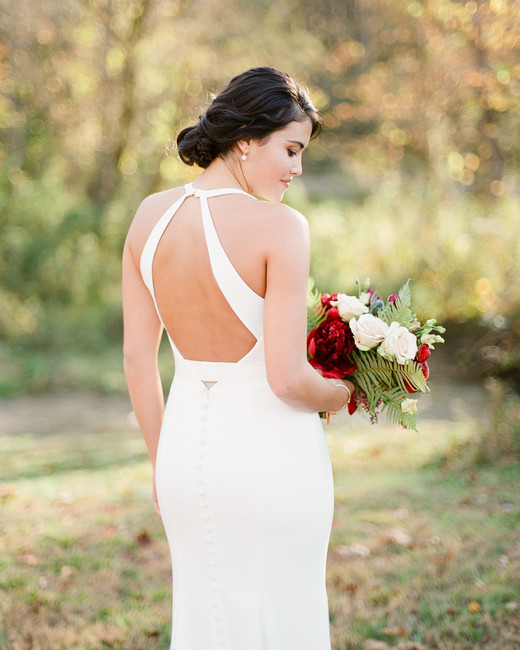 bride wearing plunging neckline open-back ivory Mikaella crepe wedding gown