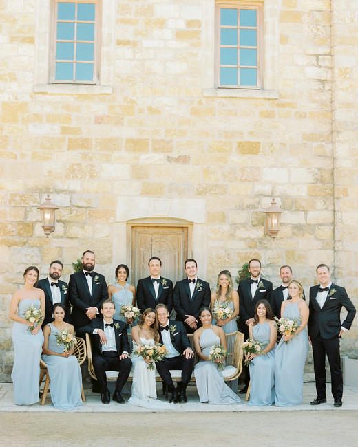 7 bridesmaids wearing slate gray chiffon dresses and 8 groomsmen wearing black and white tuxedos