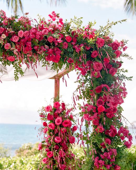 fuchsia-colored flowers and greenery covered chuppah