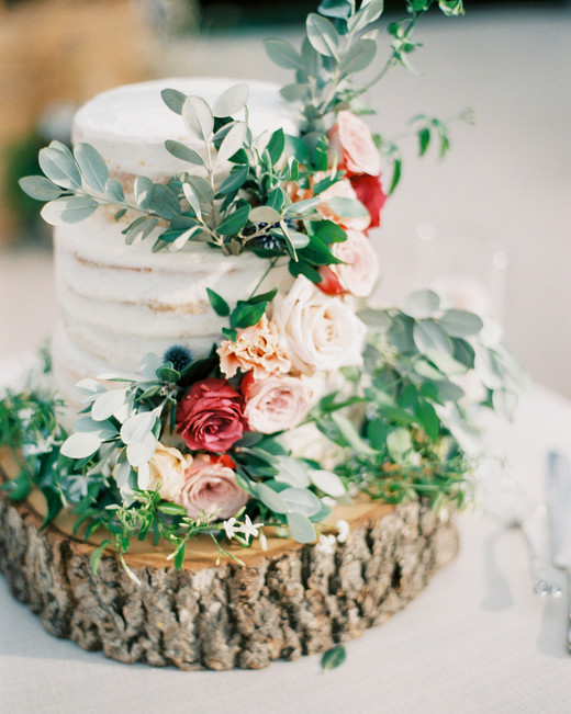 three tiered buttercream icing with floral decor on wooden slab