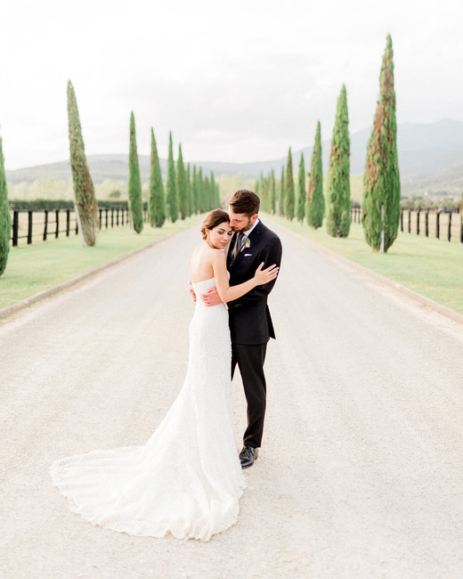 bride and groom hold each other outside on tree lined path
