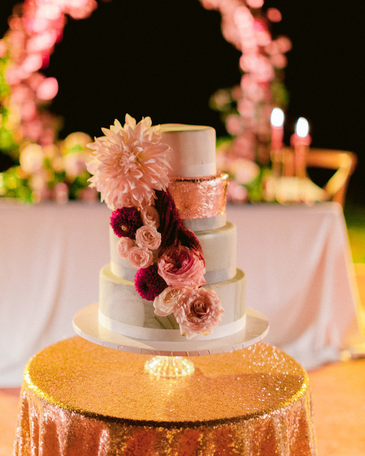 four tiered white frosted wedding cake with red and pink floral accents