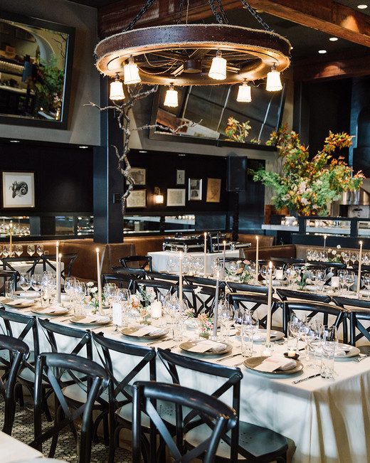 black chairs next to long tables with neutral tablescapes