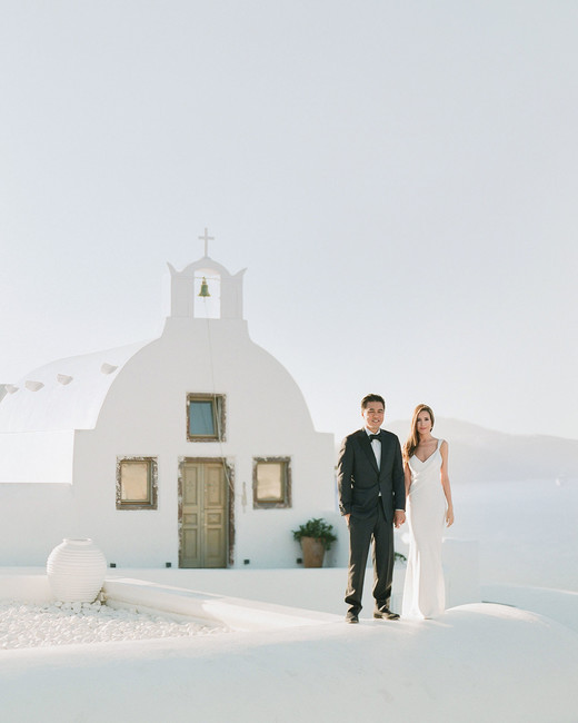 bride and groom outside of white Grecian church