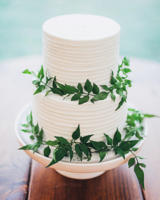 layered white wedding cake with greenery