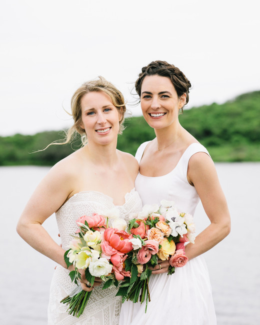 brides stand in front of water with bouquets