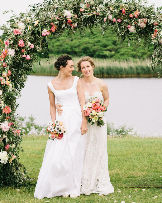 brides stand under floral arch next to water