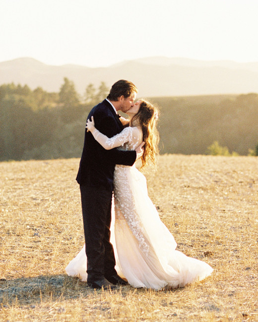 bride and groom kissing on california hillside