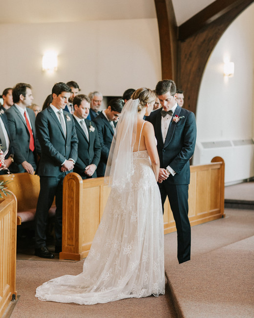 bride and groom hold hands during traditional catholic wedding ceremony