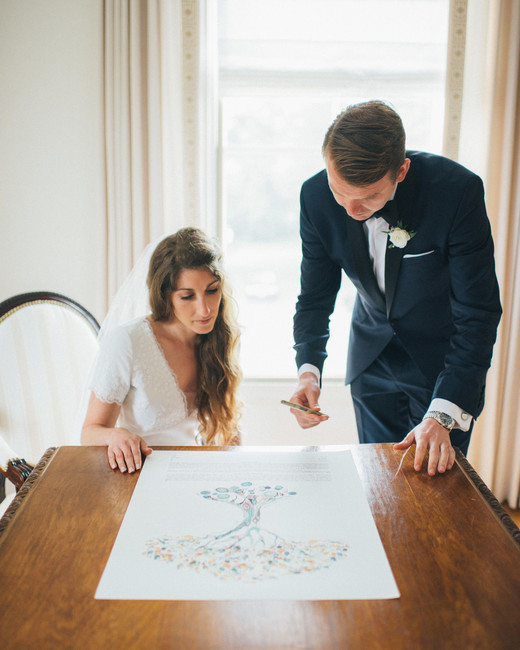 bride groom signing paper with tree print