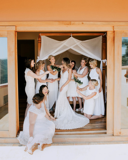 bride surrounded by female friends and family wearing white dresses