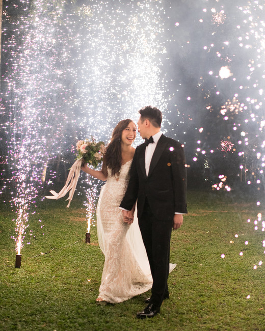 bride and groom smiling under sparklers