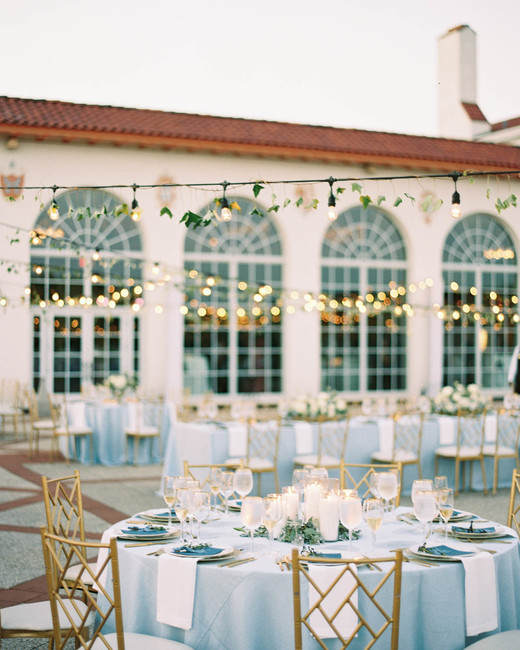 pale blue tablecloths on long and round tables with white linens, gold chairs, and tea lights