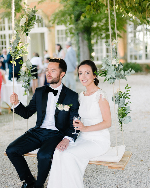 bride and groom sit on hanging swing