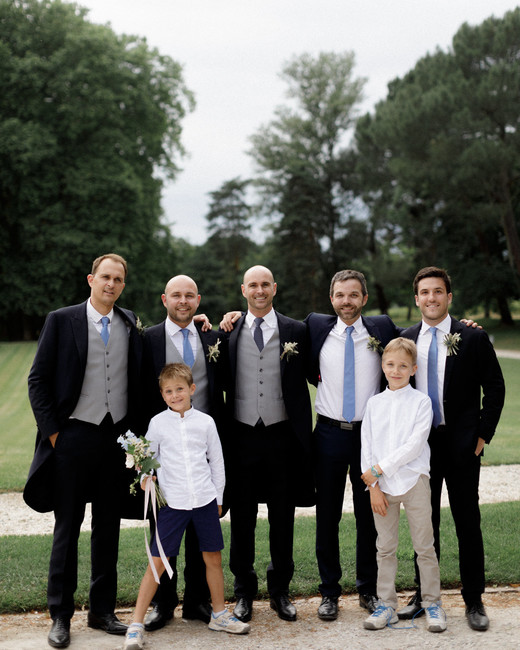 groom standing outside wedding venue with groomsmen