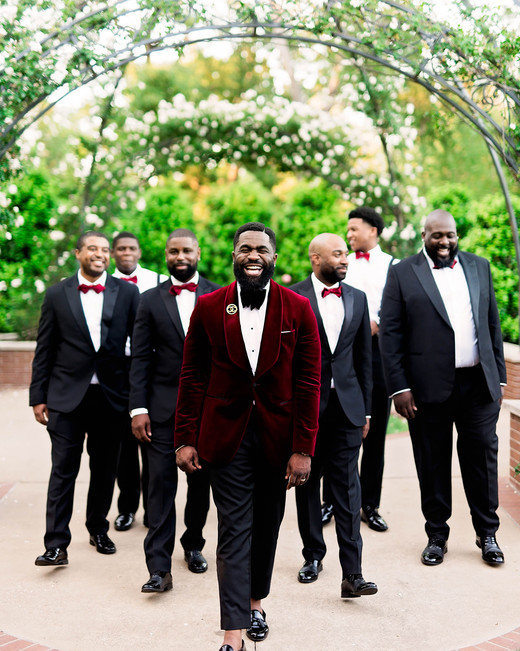 groom in red suit with groomsmen in black suits