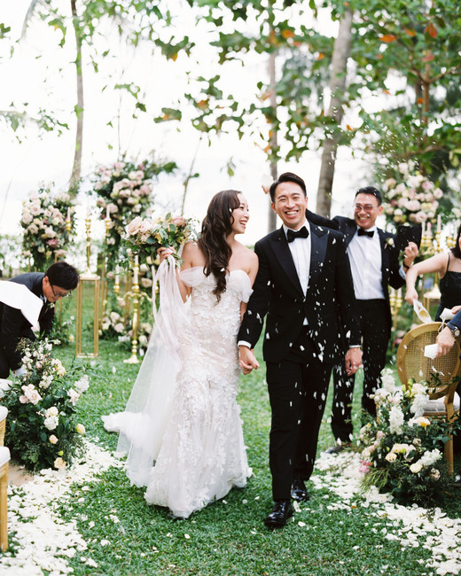bride and groom holding hands walking down recessional