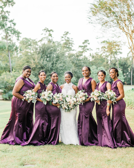 bride with bridesmaids wearing long deep violet colored dresses