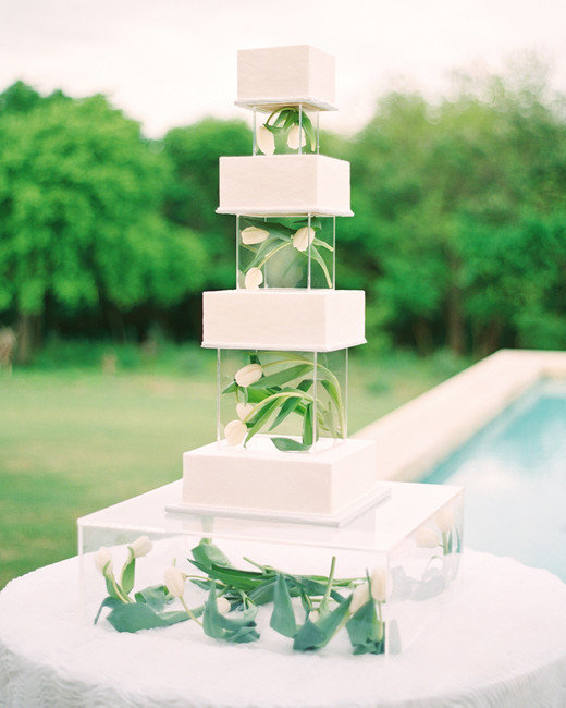 lucite cubes containing white tulips breaking up tiers of white wedding cake