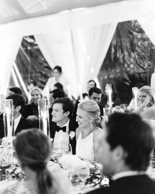 bride and groom listen to toasts during reception