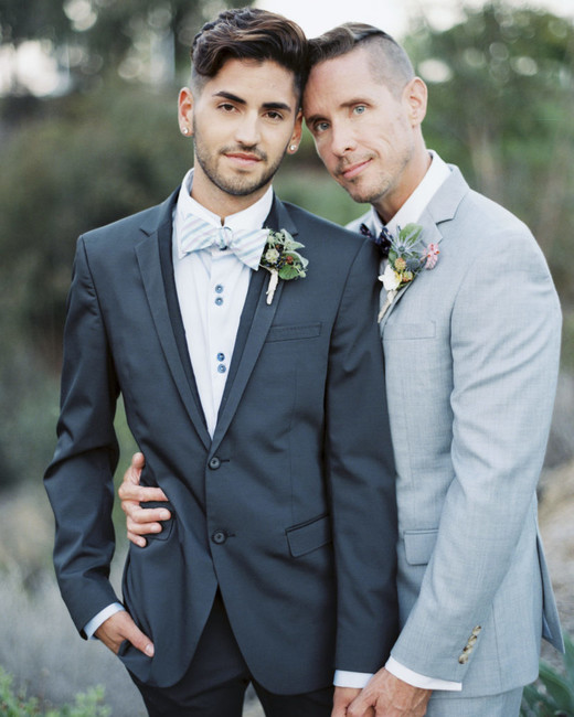 grooms wearing opposite gray shade color suits with printed bow ties