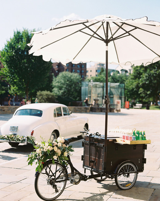 rose bicycle cart with white umbrella next to white vintage car