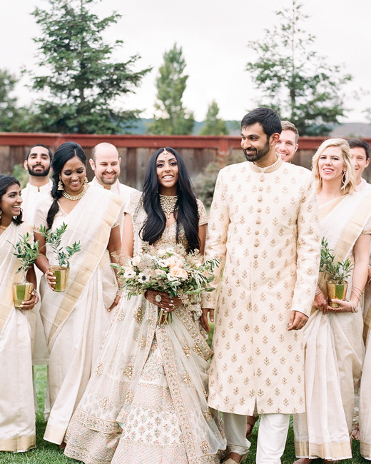 bride and groom with wedding party wearing indian wedding attire