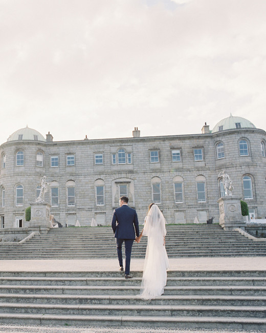 bride and groom walking up stairs at venue