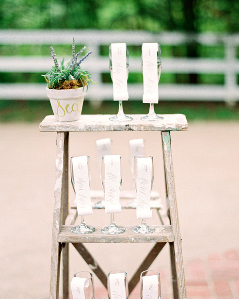 alcohol escort cards glasses on ladder with paper scrolls