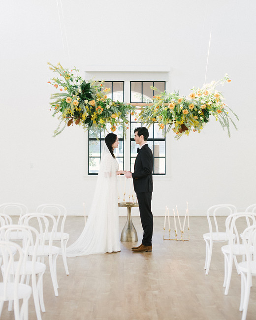 large hanging floral and greenery decor above wedding alter