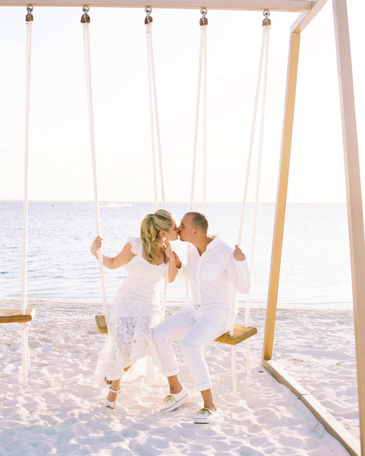bride and groom kissing on wooden rope swing set on beach