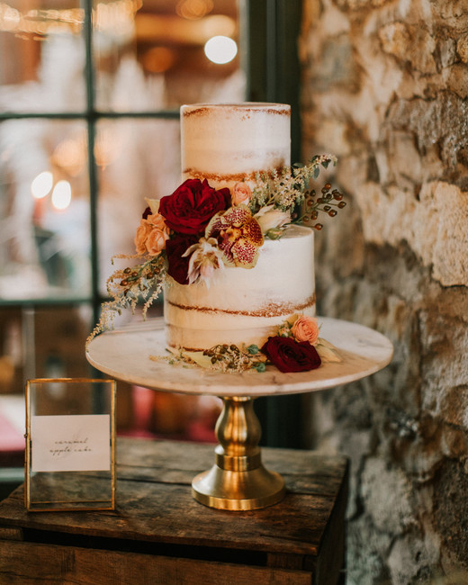 two tiered white frosted wedding cake with autumn floral accents on marble and gold cake stand