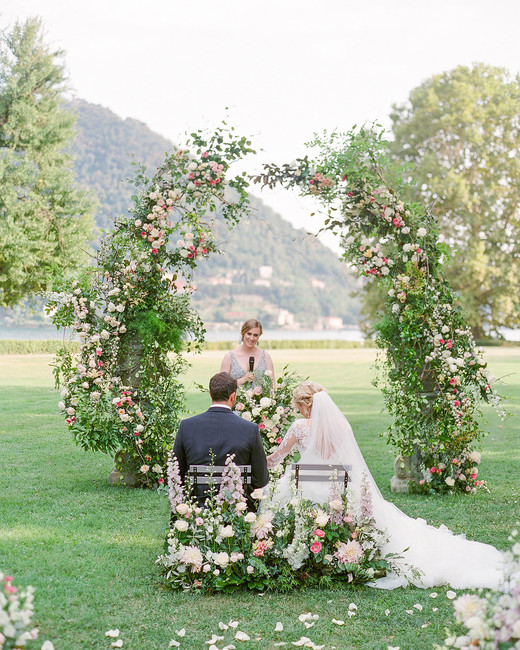 julia mauro wedding ceremony arch couple sitting in floral decorated seats