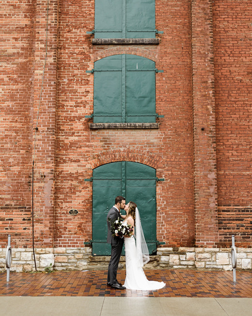 bride and groom embrace outside of distillery courtyard