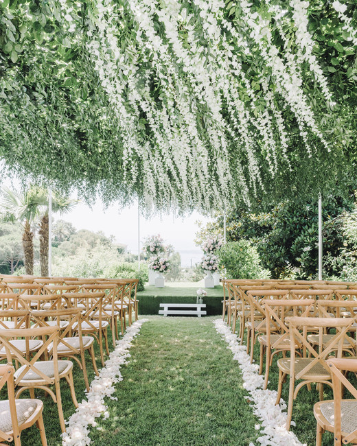 canopy of greenery hanging over wedding ceremony chairs