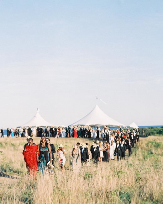 guests walk outside from cocktail hour to reception tent