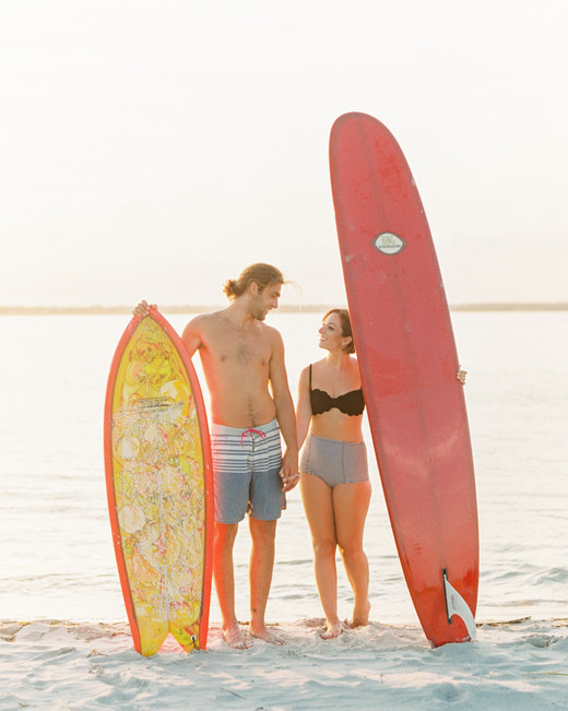 couple with surfboards engagement photo