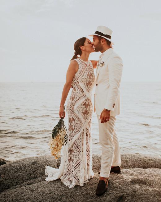 beach wedding dresses bride and groom kissing on rock
