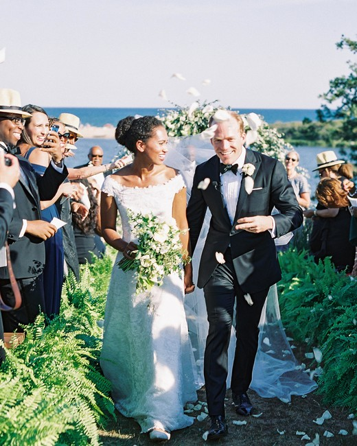 guests shower newlyweds with white petals during recessional