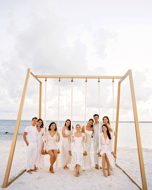 bride and groom with wedding party all wearing white on beach